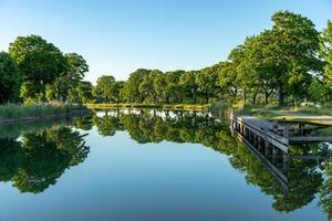 Canal gota en Suecia con aguas tranquilas muertas en la luz del sol de la tarde