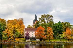 vista muy colorida de una iglesia sueca en otoño. con arboles de diferentes colores.