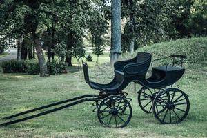 Antique black stage coach or horse carriage with wooden wheels photo