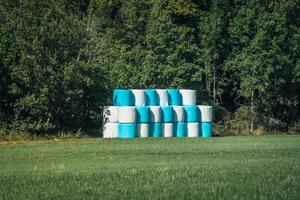 Newly harvested, large bales of hay silage in white and blue plastic wrapping