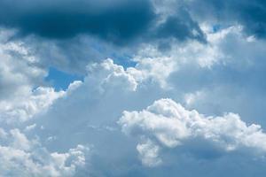 hermoso cielo con nubes blancas y grises en la luz del sol foto