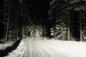 View of a slippery winter road with high beam headlights at night photo