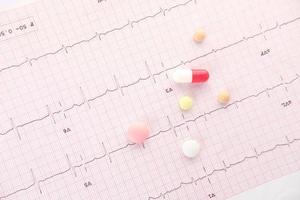 Prescription medical pills on a cardio diagram photo