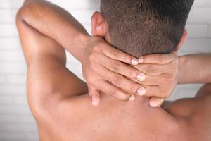 Hombre sujetando el cuello con dolor por detrás foto