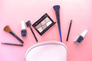 suministros cosméticos sobre fondo rosa foto