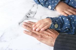 Child holding older person's hand photo