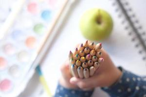 Child holding colored pencils at a work station