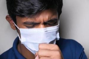 Joven tosiendo mientras usa máscara foto