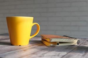 taza amarilla sobre una mesa con un cuaderno
