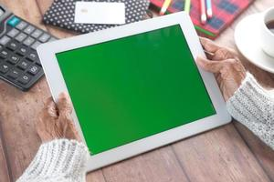 Older woman holding digital tablet with green screen photo