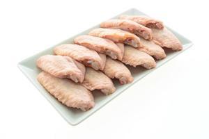 La carne de pollo cruda y el ala en la placa blanca. foto
