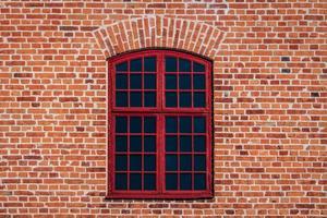 Pared de ladrillo con ventana abovedada roja foto