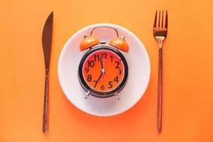 Despertador en placa sobre fondo naranja foto