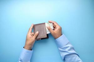 Sacar dinero en efectivo de la billetera sobre fondo azul.