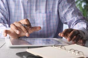 La mano del hombre trabajando en tableta digital en el escritorio de oficina