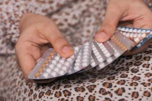 mujer sosteniendo muchos paquetes de control de la natalidad foto