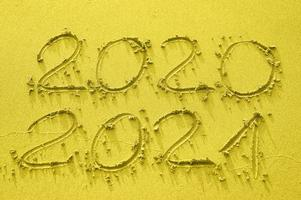 Inscription on the gold sand 2020 and 2021, toned in trend color of the year 2021 photo