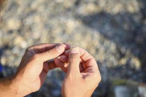 Las manos del hombre atando un hilo de pescar en un anzuelo de pesca foto