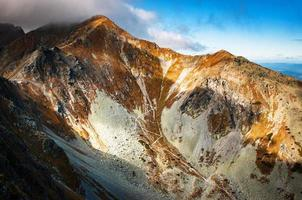 Brown mountain with clouds photo