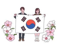 un joven estudiante y una estudiante están de pie con una gran bandera coreana. Las flores de Sharon están floreciendo a su lado. vector
