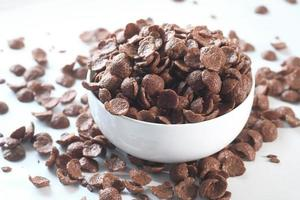 Close up of chocolate corn flakes in a bowl on white photo