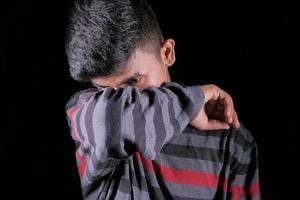 Man sneezing into elbow on black background photo