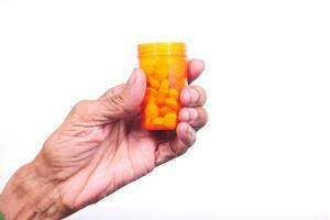 La mano del anciano sosteniendo el frasco de pastillas sobre fondo blanco.
