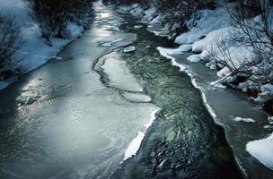 Dark winter scene with a frozen river