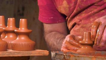 Mann in der Werkstatt, der Vasen aus Ton herstellt