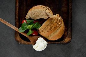 Desayuno con queso crema, tomates y bagels de grano sobre una superficie gris
