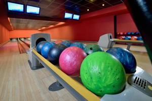 Bowling balls and wooden lanes in a bowling hall