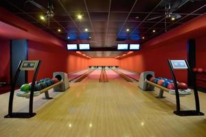 Bowling balls and wooden lanes in a bowling hall photo