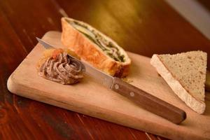 Sandwiches with homemade chicken liver on a wooden cutting board