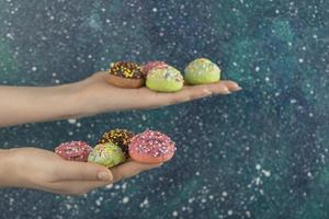 Hands holding colorful sweet small doughnuts with sprinkles photo