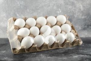 Huevos de gallina crudos en una caja de huevos sobre un fondo de mármol foto