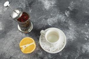 Una taza de bebida de cerámica blanca con una tetera sobre un fondo de mármol foto