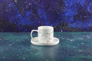 Una taza de bebida de cerámica blanca sobre un fondo brillante foto