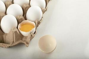 Uncooked chicken eggs in a carton container photo