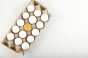 Raw chicken eggs in a carton container photo