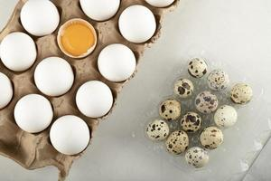 Raw chicken eggs in a carton container and quail eggs photo