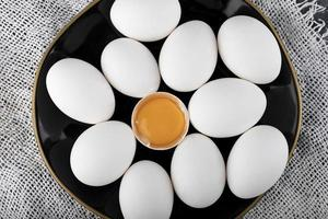 White eggs and yolk on a black plate photo
