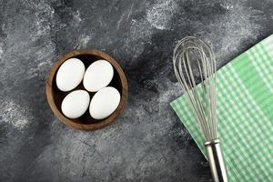 Bowl of raw eggs and a whisker on a marble background photo