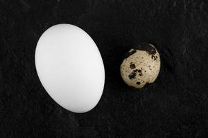 Chicken and quail eggs on a black background photo