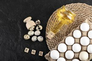 Fresh farm quail eggs, chicken eggs, and olive oil with wooden blocks with the word Egg on a black background photo