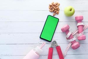 teléfono inteligente con equipamiento deportivo sobre suelo de madera