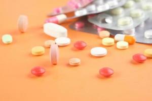 Cerca de muchas píldoras y cápsulas de colores sobre fondo naranja