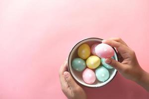 mano del niño recogiendo coloridos huevos de pascua foto