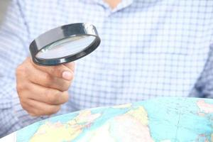 Person using a magnifying glass to look at a world map photo