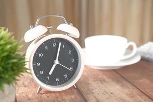 despertador y taza de té en la mesa