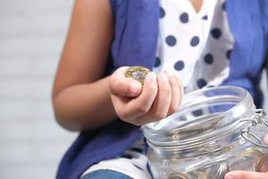 Child girl putting coins in a jar photo